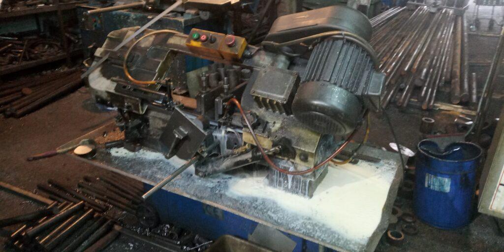 Резка метала пилой на производстве.